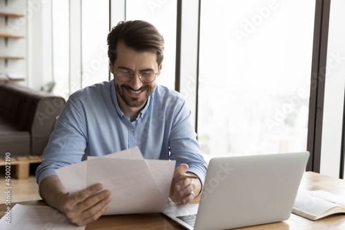 Cuadros en Lienzo Happy business professional in glasses reviewing official legal documents, reading received paper letter with good news, bank notice, approved loan agreement