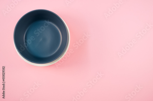 Fotografiet Top view of empty ceramic black and white plates on a pink background