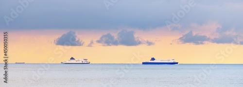Fotografie, Obraz Large ships sailing near the coast of France at the Strait of Dover (Cap Blanc Nez, Pas de Calais) during sunset
