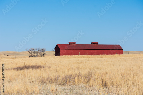 Fotografering Red Barn On A Dry Field With Blue Sky