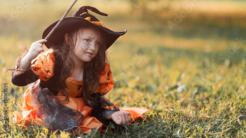Photo Little witch girl conjures magic wand on Halloween.