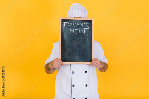 Obraz na plátně Chef cook wearing a white kitchen hat and jacket covers his face with a blackboa