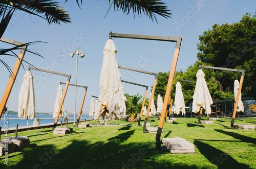 Sun beds and umbrellas on a beautiful tropical beach at the Adriatic coast in Slovenia Fototapeta