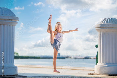 Foto Gymnast teenage girl posing on embankment against background of the sea and sky
