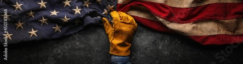Fotografie, Obraz Worn work glove holding old US American flag