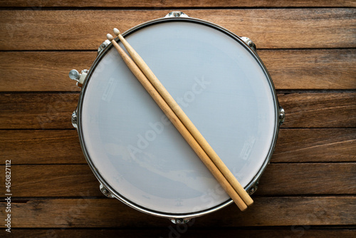 Fotografering Drum stick and drum on wooden table background, top view, music concept