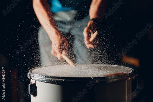 Photographie Close up drum sticks drumming hit beat rhythm on drum surface with splash water