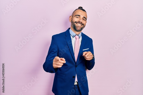 Fototapeta Young hispanic man wearing business suit and tie pointing fingers to camera with happy and funny face