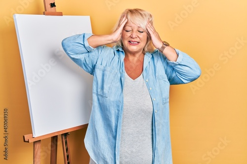 Fotografiet Middle age blonde woman standing by painter easel stand suffering from headache desperate and stressed because pain and migraine