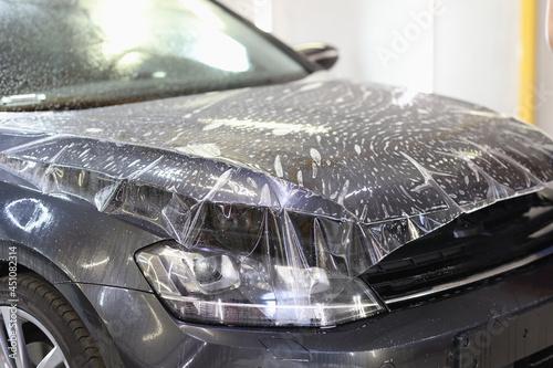 Fototapeta Polyurethane vinyl film pasted on hood of car closeup