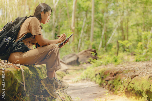 Fotografia Biologist or botanist recording information about small tropical plants in forest