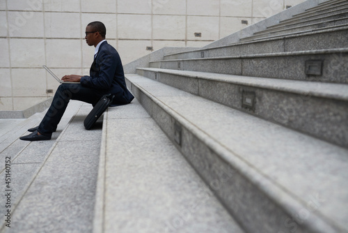 Side view of software developer in suit sitting on steps outdoors and coding on laptop