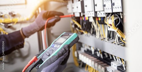 Electrician engineer tests electrical installations and wires on relay protection system Fototapet