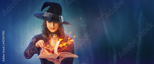 Fotografia Halloween Witch girl with magic Book of spells portrait