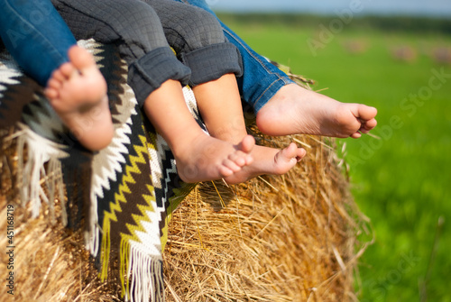 Fotografie, Tablou Four children's bare feet on the background of a haystack and a striped plaid