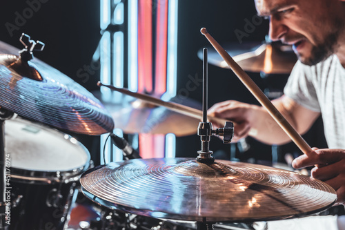 A male drummer plays drums with drum sticks. Fototapet