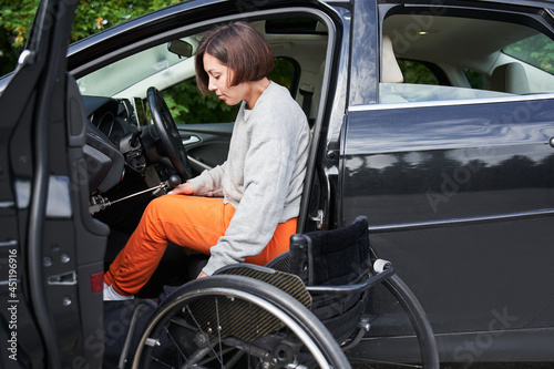 Foto Disabled woman sitting on wheelchair boarding into her car