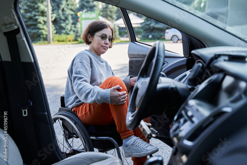 Photographie Woman opening door of her car outdoors and replacing inside from her wheelchair
