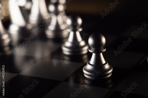 Fotografiet Selective-focus shot of black pawn chess figures on the board with bokeh lights