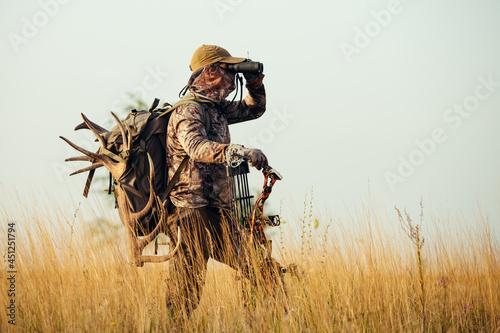Valokuvatapetti Archery hunter scouting for his next target.