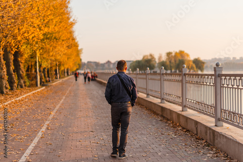 Leinwand Poster A young man walks along the autumn promenade