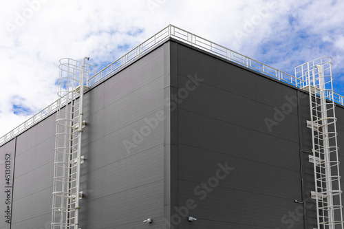 Corner of industrial building with two white metal fire escapes against sky Fototapet