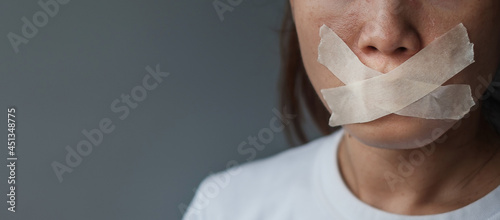 Fotografering woman with mouth sealed in adhesive tape