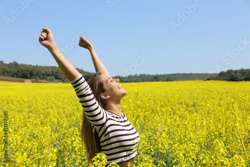 Tela Excited woman raising arms in a yellow field celebrating spring