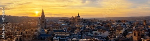 Fotografija Panoramic view of skyline of old part of the city with small streets in a colorful sunset between the belfry of the tower of the old cathedral of Toledo in orange sunset, Spain