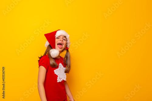 Fotografia Little girl wearing Santa hat sticking tongue out
