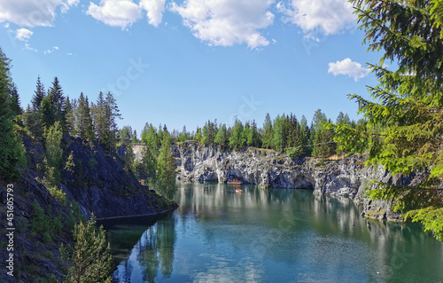 Fotografia View from the observation deck of the emerald water of the Marble Canyon in the Ruskeala Mountain Park with the reflection of the sky and clouds on a sunny summer day
