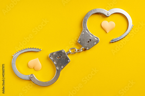 Obraz na plátne Opened handcuffs on yellow background.
