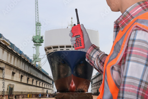 Stampa su Tela Close up hand holding walkie talkie, prow ship, Big ship under repairing on floa