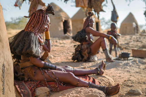 Obraz na plátně Himba women sitting outside their huts in a traditional Himba village near Kamanjab in northern Namibia, Africa
