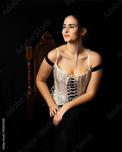 Fotografía Mulher morena vestida com corpete branco, em fundo preto.