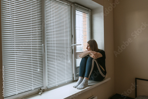 Fotografija Young woman looking downward while sitting near a window