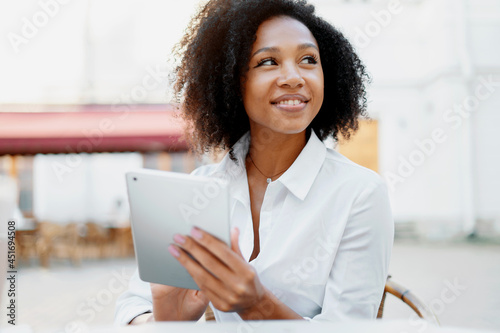 Fotografia A beautiful Afro-looking woman is surfing the Internet on a tablet in a summer cafe
