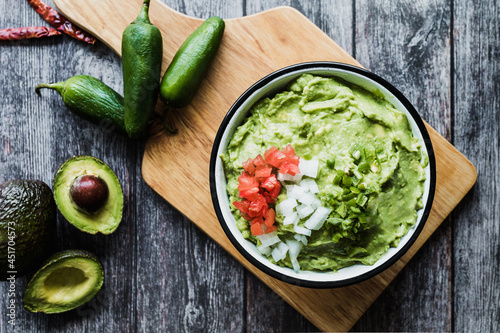 Canvastavla Bowl of Guacamole next to fresh ingredients on a wooden table in Mexico