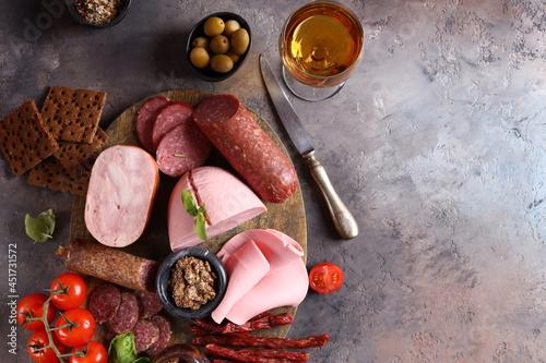 Obraz na plátně assortment of sausages and ham on wooden background, antipasti, appetizer