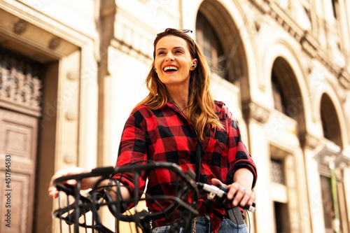 Young blonde woman on bicycle on the street Fototapeta