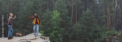 Fotografie, Tablou happy couple with smartphones standing on rocky cliff during rain, banner