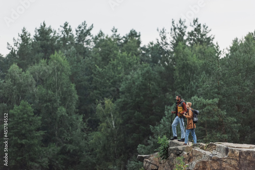 Tablou Canvas couple with hiking sticks standing on rocky cliff