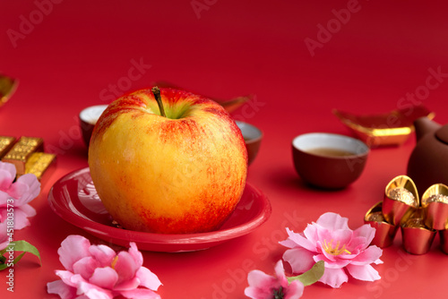 Red envy apple in red plate ,accessories on lunar new year & chinese new year vocation concept and flower on red background Fototapet