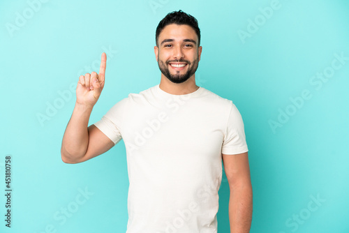 Young arab man isolated on blue background pointing up a great idea Tapéta, Fotótapéta