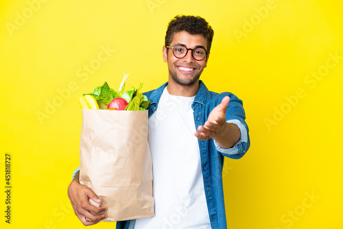 Fotografia Young Brazilian man holding a grocery shopping bag isolated on yellow background