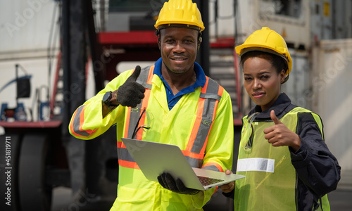 Fotografering Black African male and female worker showing thumbs up with laptop working at wa