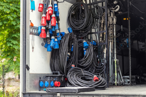 Obraz na plátně Open cargo box of filming movie set production equipment transport truck van vehicle with many electrical cables wire, rack and sockets on city streey outdoors