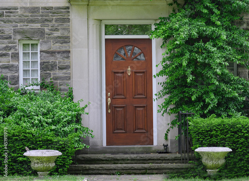 wood grain front door of old stone house with shrubbery Fototapeta