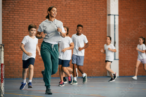Billede på lærred Physical education teacher and group of elementary students run while warming up at school gym