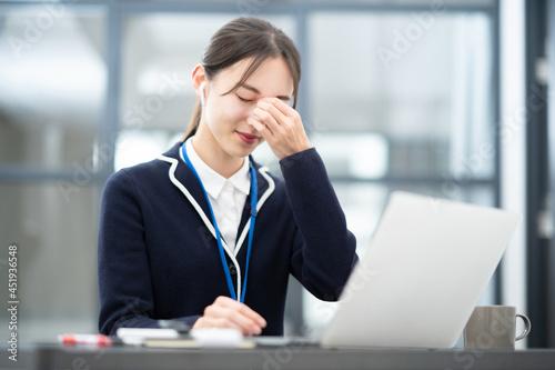 Fotografia 仕事中、頭痛に悩む女性